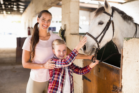 Portrait of sisters stroking horse while standing in stable Stock Photo