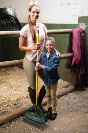 Portrait of female jockey with sister holding rake while standing in stable