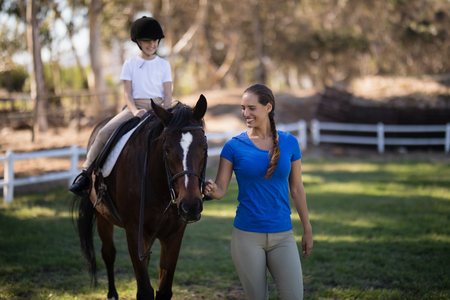 Smiling female jockey holding bridle while sister sitting on horse at field