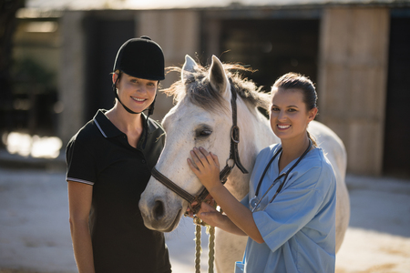Portrait of smiling female vet with jockey standing by horse at barn