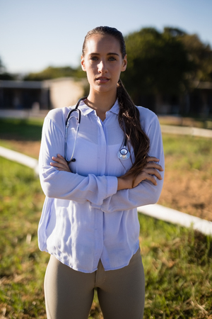 Portrait of female vet with arms crossed standing on field at barn