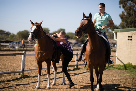 Female friends preparing for horse background during sunny day