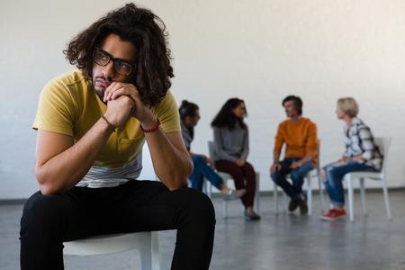 예술 클래스에서 백그라운드에서 논의하는 친구와 함께 의자에 앉아있는 동안 멀리 찾고 남자