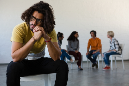Man looking away while sitting on chair with friends discussing in background at art class