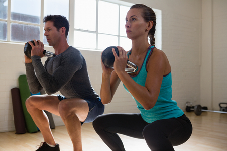 Athletes looking away while lifting kettlebells in gym