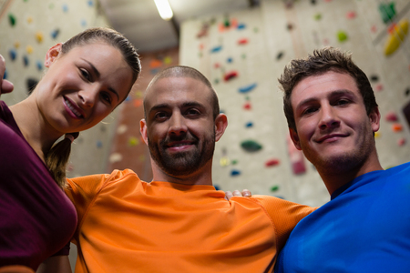 Low angle portrait of confident male trainer with athletes in gym