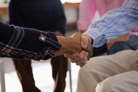Sluit omhoog van vrienden die handdruk doen terwijl het zitten in kunstklasse Stockfoto
