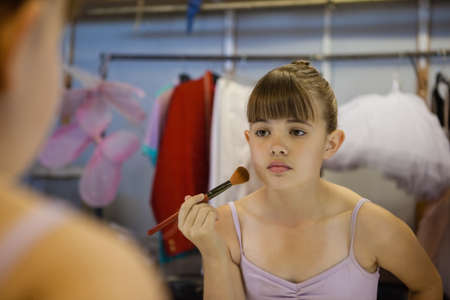 mirror image: Cropped image of girl applying blush while reflecting in mirror in dressing room