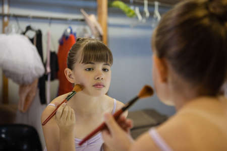 mirror: Close up of girl doing make up while reflecting in mirror