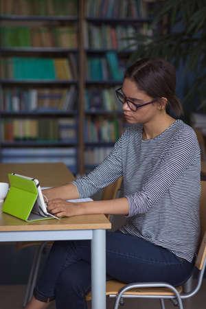 Estudiante de la universidad femenina con tableta digital mientras estudiaba en el escritorio en el aula