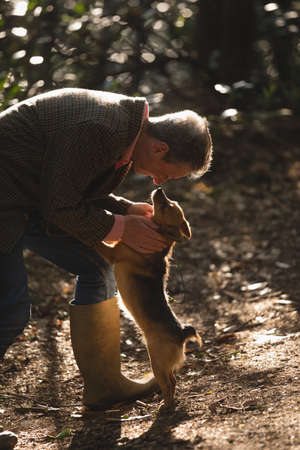Mature man with his pet dog in forest LANG_EVOIMAGES