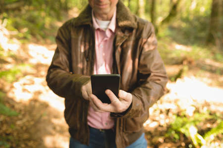 Mid-section of man taking selfie with mobile phone in forest LANG_EVOIMAGES