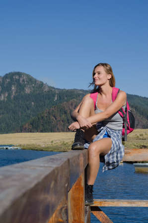 Full length of smiling female hiker sitting on railing at pier against clear blue sky
