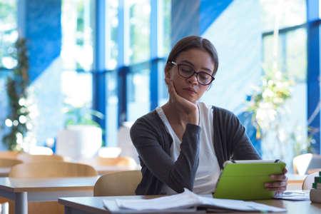 Adolescente con la mano en la barbilla con la computadora de la tableta mientras está sentado en el escritorio en el aula LANG_EVOIMAGES