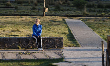 Female athlete sitting on retaining wall during sunny day LANG_EVOIMAGES