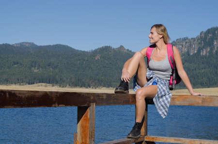 Smiling female hiker sitting on railing at pier against blue sky