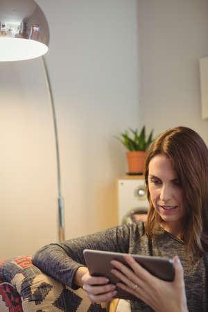 modern living room: Woman using digital tablet in living room at home LANG_EVOIMAGES