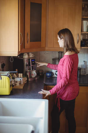 kitchen cabinets: Woman using coffeemaker in kitchen at home LANG_EVOIMAGES