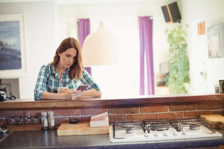 kitchen cabinets: Woman using mobile phone while having coffee in kitchen at home LANG_EVOIMAGES