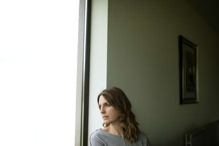 contemplated: Contemplated woman sitting on window sill at home