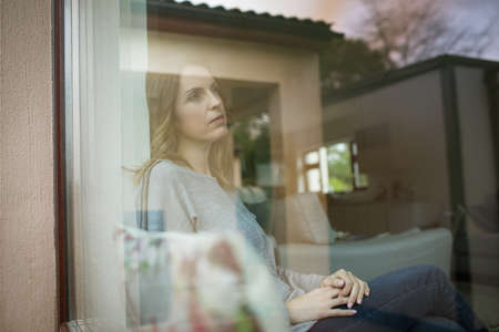 contemplated: Thoughtful woman sitting by window seen through glass LANG_EVOIMAGES