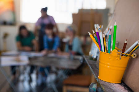 easel: Close up of colored pencils in bucket on easel with students in background at art class LANG_EVOIMAGES