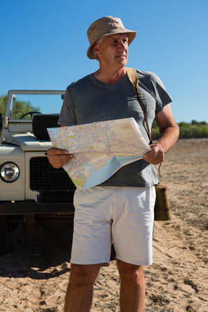 Man looking way while holding map by off road vehicle on field