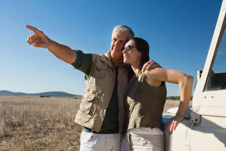 Man with woman pointing by off road vehicle on landscape