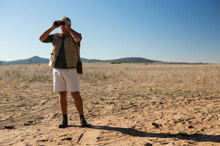 Man looking through binocular while standing on landscape during sunny day