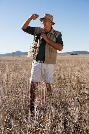 Man with binocular shielding eyes while standing on grassy landscape
