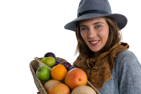 Portrait of smiling woman carrying fruits and vegetables in basket while standing against white background Stock Photo
