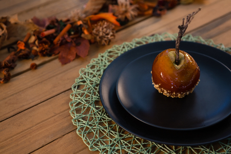 High agnle view of caramelized apple served in plate on wooden table