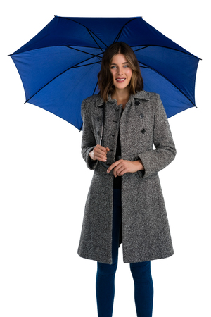 Portrait of smiling young woman holding umbrella while standing against white background