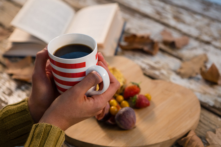 Cropped hand on woman having coffee at table during autumn