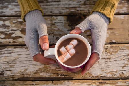 Cropped  hand of woman having hot chocolate at wooden table
