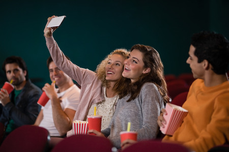 Friends taking a selfie while watching movie in theatre Stock Photo