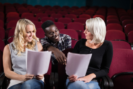 Mid-section actors reading their scripts on stage in theatre