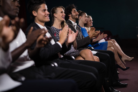 Group of people applauding in movie theatre