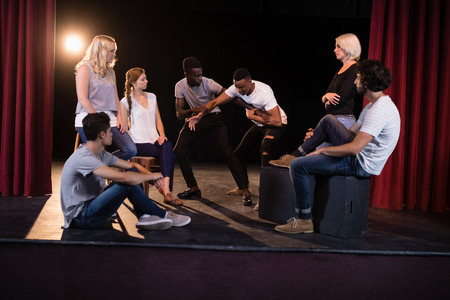 Actors practicing play on stage in theatre