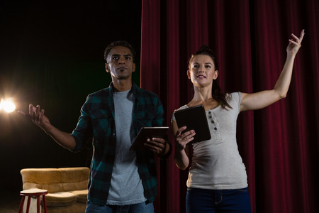Actors rehearsing on stage while using digital tablet in theatre Foto de archivo