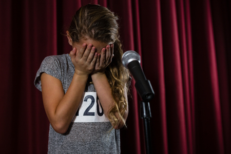 Girl covering her face with hand on stage in theatre Stock Photo - 84503241