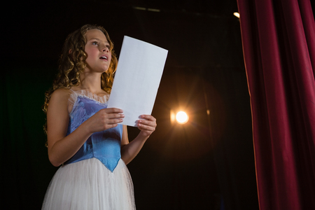 Female artist reading her scripts on stage in theatre