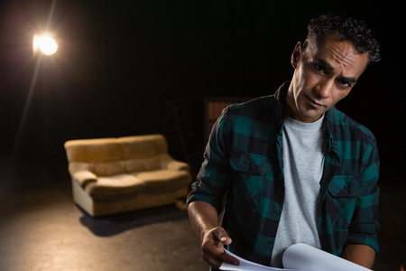 Portrait of actor holding his scripts on stage in theatre Stock Photo