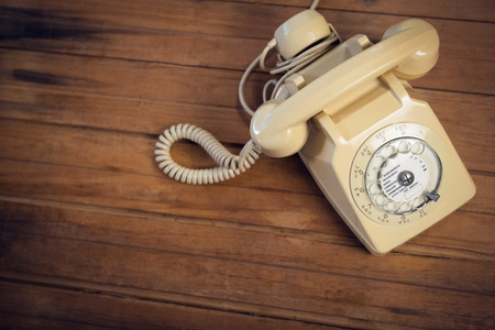High angle view of landline phone on wooden table