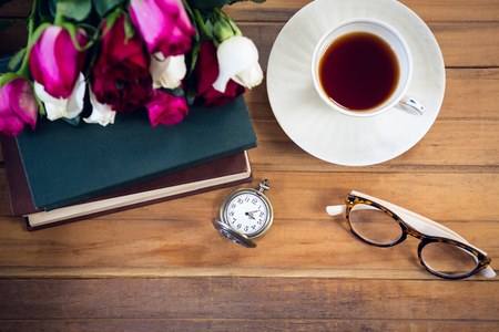 Overhead view of eyeglasses by stopwatch and tea with books on table Stock Photo