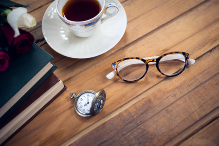 Close up of eyeglasses by stopwatch and tea with books on table Stock Photo