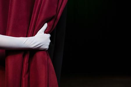 Primer plano de la mano en un guante blanco tirando de la cortina Foto de archivo - 84481492