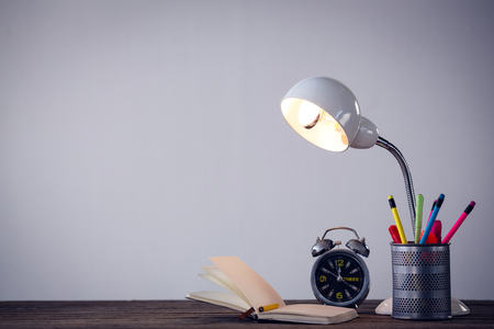 Illuminated lamp with desk organizer by book and alarm clock on table against wall Stock Photo