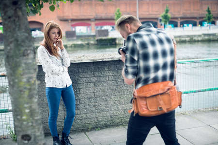 Rear view of photographer photographing fashion model while standing in city LANG_EVOIMAGES
