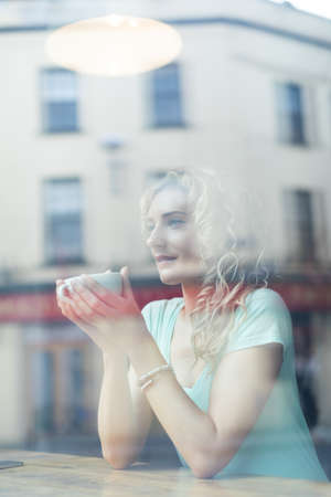 contemplated: Thoughtful woman looking away while sitting in cafe seen through window at cafe LANG_EVOIMAGES